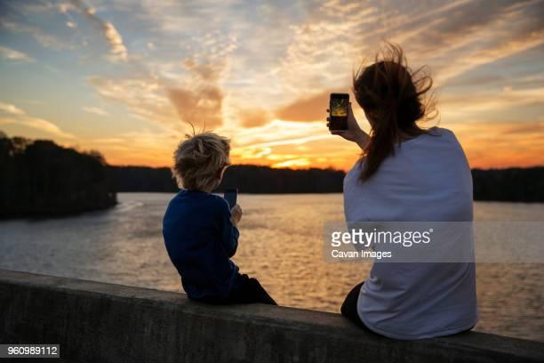 boy and girl sitting on ledge photographing sunset - ノースカロライナ州ローリー ストックフォトと画像