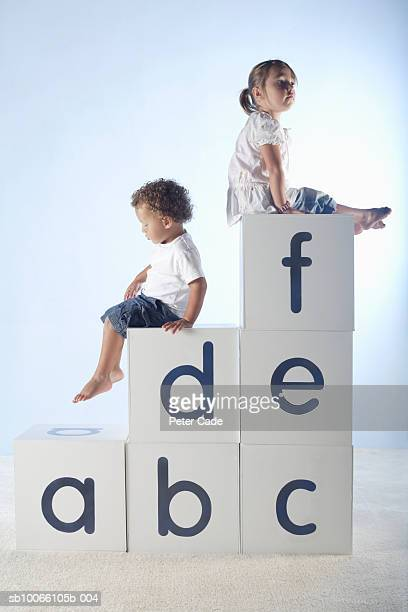 Boy and girl (2-5) sitting on lettered white boxes, side view