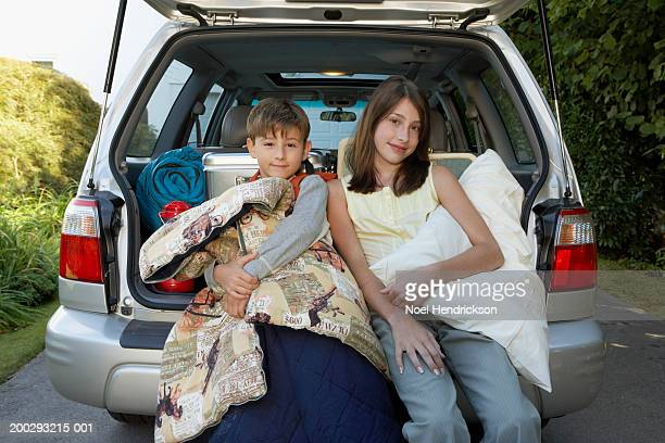 Boy (7-9 years) and girl (13-15 years) sitting on rear bumper of car, holding sleeping bag and pillow, smiling, portrait