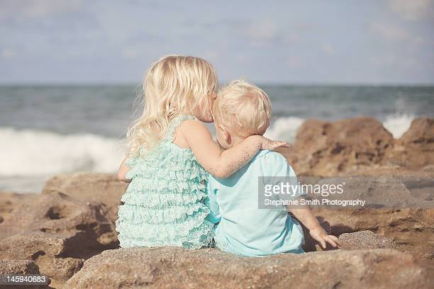 boy and girl sitting on rocks at beach - jupiter florida stock pictures, royalty-free photos & images