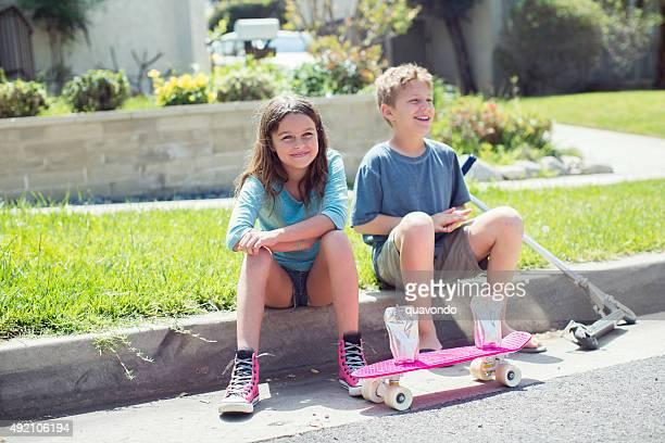 Jungen und Mädchen sitzt auf dem Bürgersteig mit skateboard und scooter