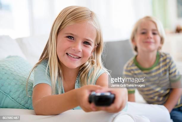 Boy (4-5) and girl (6-7) sitting on sofa