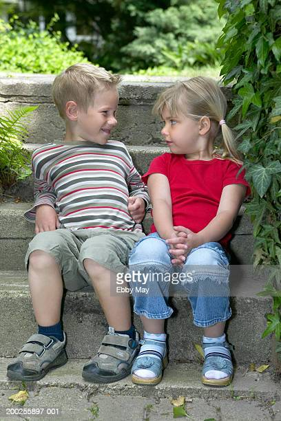 Boy and girl (4-6) sitting on steps outdoors, looking at each other