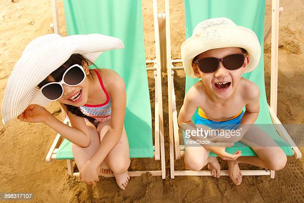 Boy and girl sitting on sun loungers