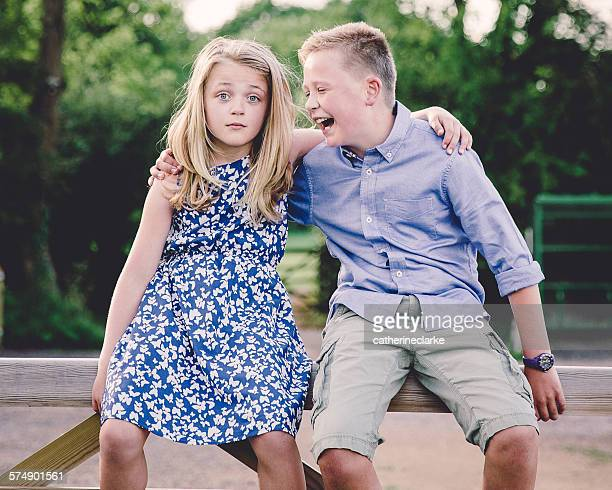 Boy and girl sitting on wooden gate with their arms around each other