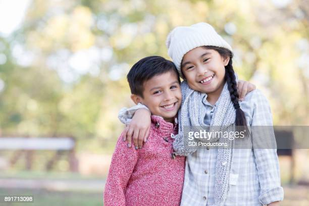 Boy and girl smile for camera outside