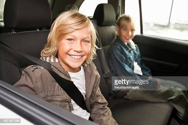 Boy and girl smiling while sitting in a car