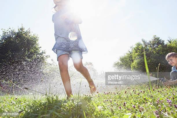 Boy and girl splashing with water in garden