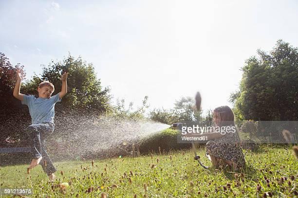 Boy and girl splashing with water in garden