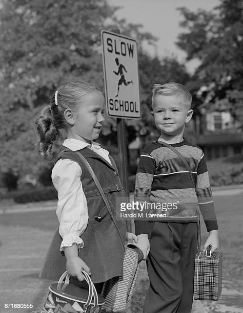 boy and girl standing at road sign - {{relatedsearchurl(carousel.phrase)}} ストックフォトと画像