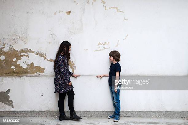 Boy and girl standing by wall looking at each other
