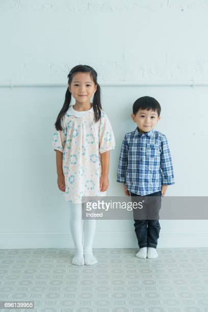 Boy and girl standing by wall, smiling