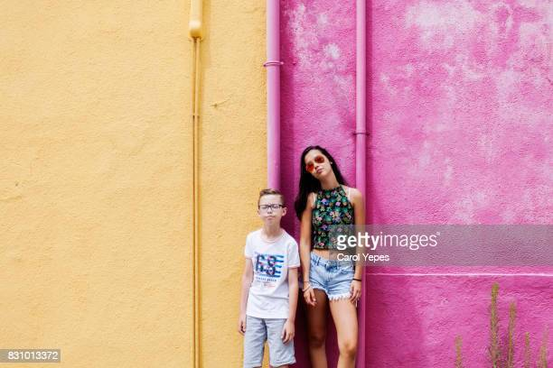 boy and girl standing in front a pink and yellow  wall