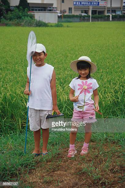 Boy and girl standing in rice paddy