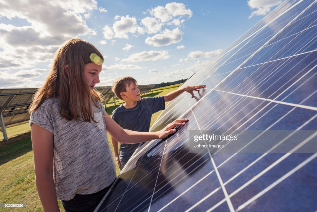 Boy and girl standing next to solar panels : Stock Photo