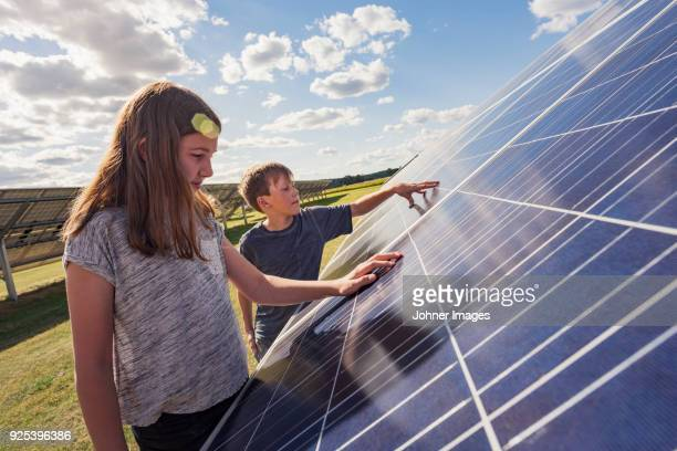 boy and girl standing next to solar panels - energieindustrie stock-fotos und bilder