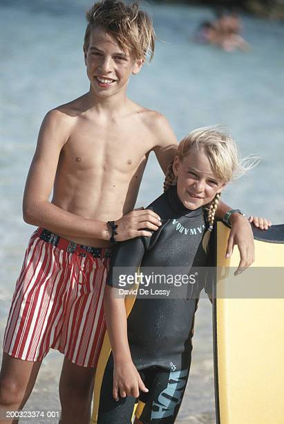 Boy (10-13) and girl (6-7) standing on beach, portrait