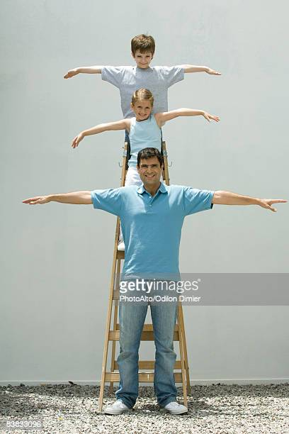 boy and girl standing on ladder with arms in the air, father standing on the ground, all smiling at camera - superman stock pictures, royalty-free photos & images