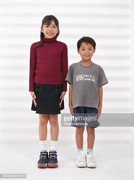 Boy (4-7) and girl (8-9) standing side by side, portrait