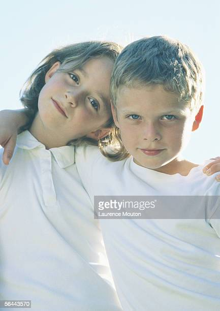 Boy and girl standing with arms around each other's shoulders, portrait