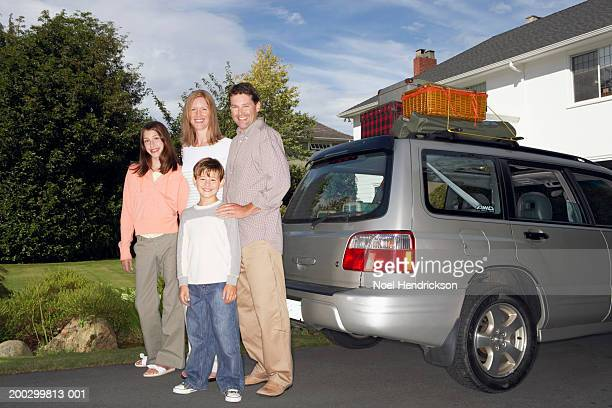 boy and girl (8-13 years) standing with parents beside car on drive, smiling, portrait - 14 15 years stock pictures, royalty-free photos & images
