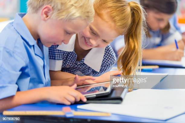boy and girl students working on a digital tablet - uniform stock pictures, royalty-free photos & images