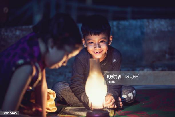 Boy and girl studying in oil lamp