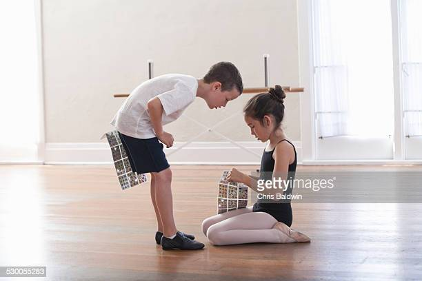 boy and girl swapping stickers in ballet school - little girls bent over stock photos and pictures