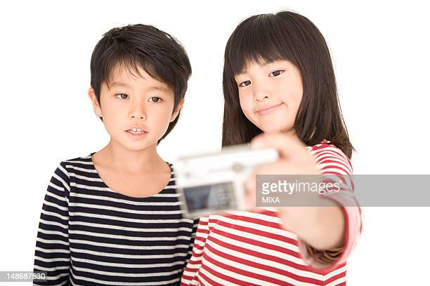 Boy and girl taking picture with digital camera