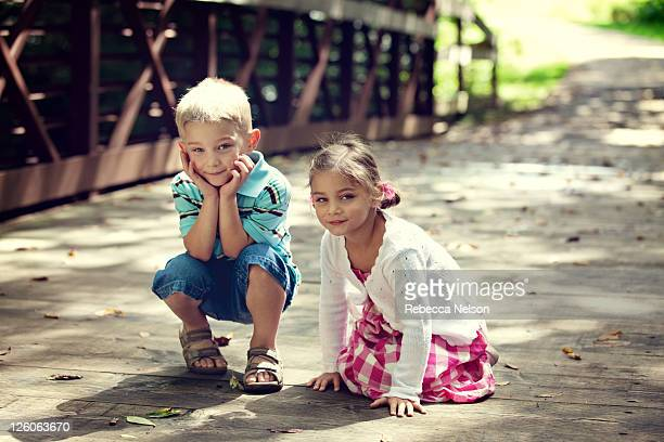 boy and girl twins on nature preserve bridge - rebecca nelson stock pictures, royalty-free photos & images
