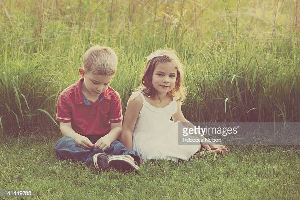 Boy and girl twins sitting in front of tall grass
