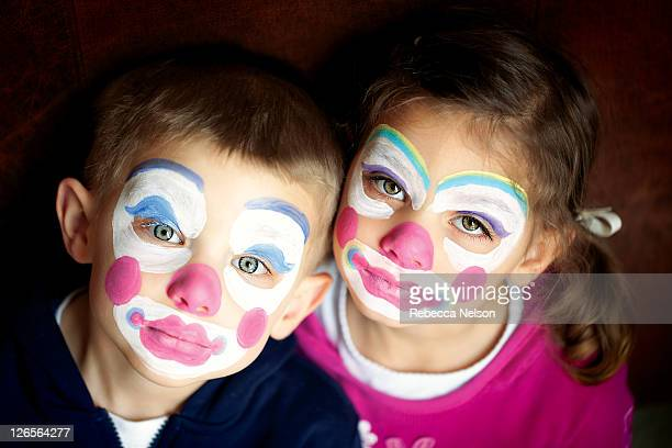 Boy and girl twins wearing clown face paint