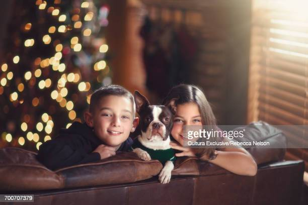 Boy and girl twins with their Boston Terrier dog in front of Christmas tree