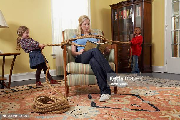 boy and girl (5-7 years) tying mother with rope in living room - junge gefesselt stock-fotos und bilder