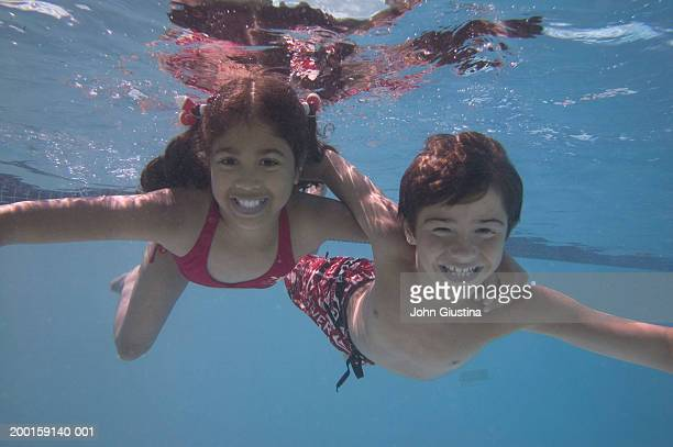 Boy and girl (10-12) underwater, smiling, portrait