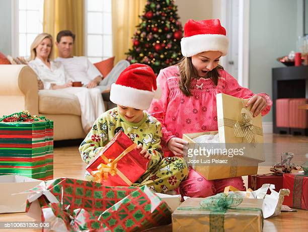 Boy (6-7 years) and girl (8-9 years) unwrapping Christmas presents in living room, parent sitting in background
