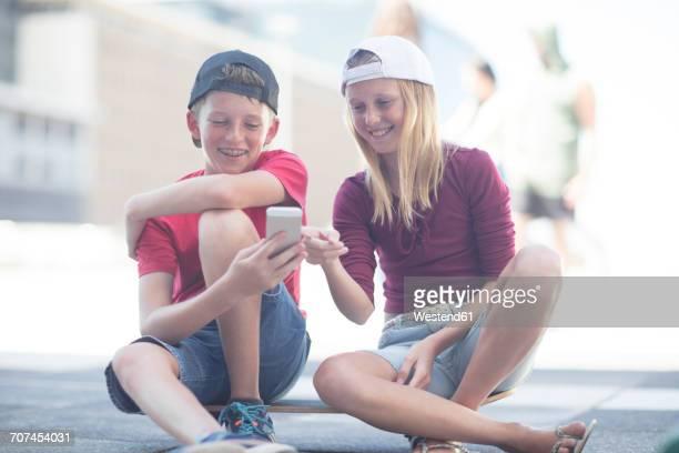 Boy and girl using smart phone, sitting on skateboard