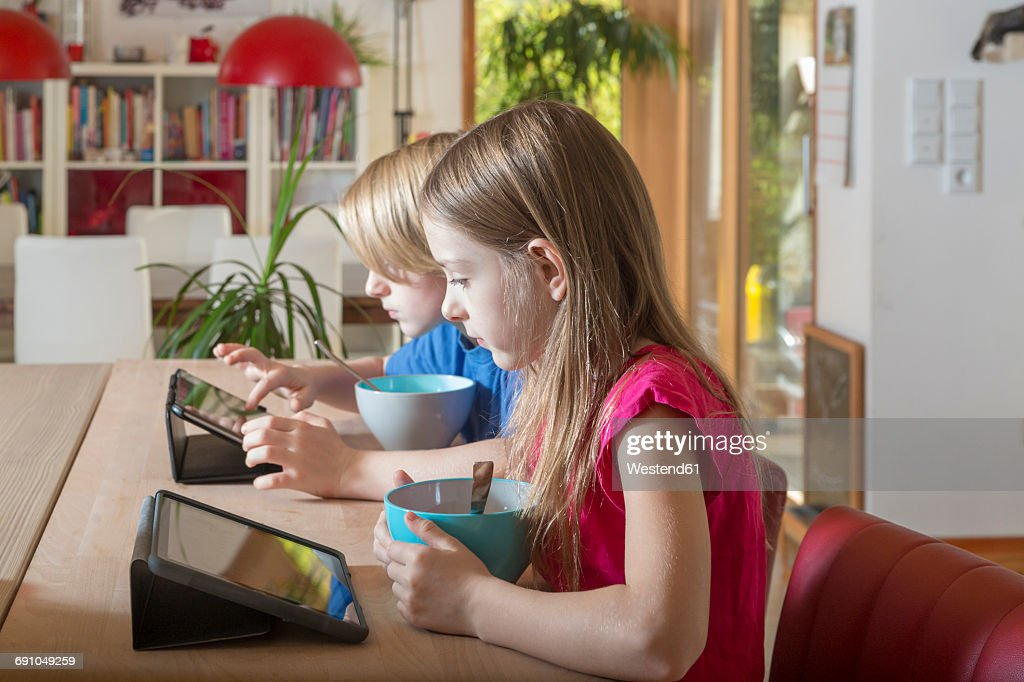 boy and girl using tablets at breakfast table stock photo getty images