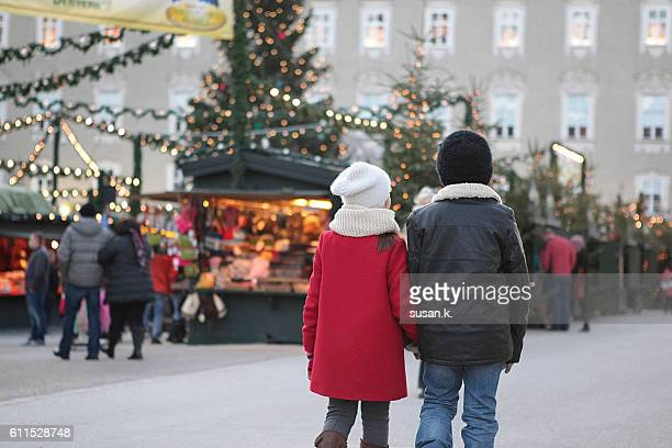 Boy and girl walking hand in hand at the christmas market