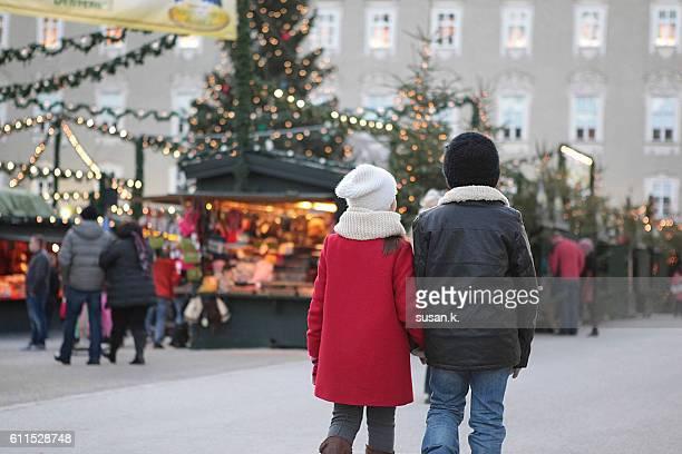 boy and girl walking hand in hand at the christmas market - salzburg stock-fotos und bilder