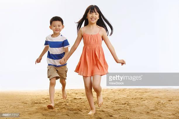 boy and girl walking on beach hand in hand - girls with short skirts - fotografias e filmes do acervo
