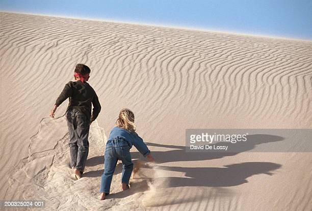 boy and girl walking on desert, rear view - little girls bent over stock photos and pictures