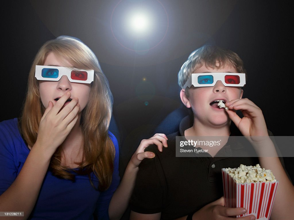Boy and girl watching 3-D movie eating popcorn : Stock Photo