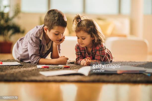 Boy and girl watching cartoons on mobile phone while relaxing on carpet at home.