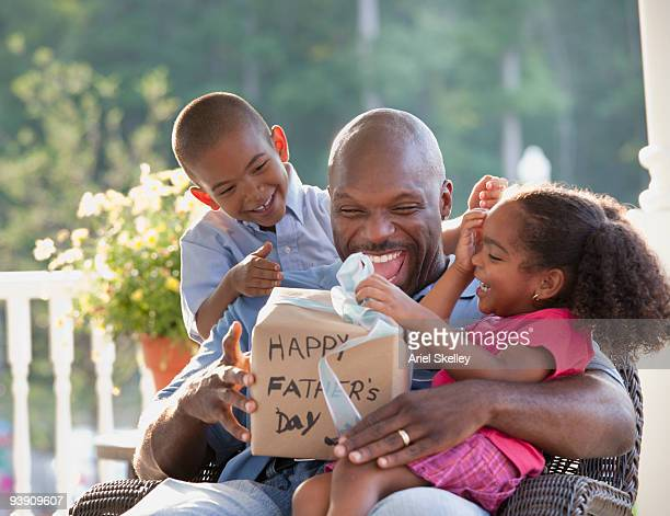 boy and girl watching father open father's day gift - fathers day stock pictures, royalty-free photos & images