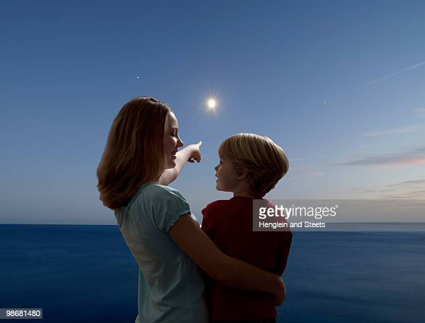 boy and girl watching the moon rising
