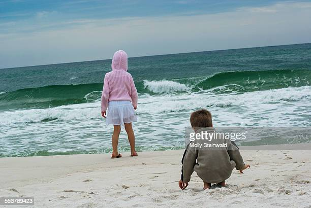 Boy and girl watching waves from shore at Pensacola Beach FL.