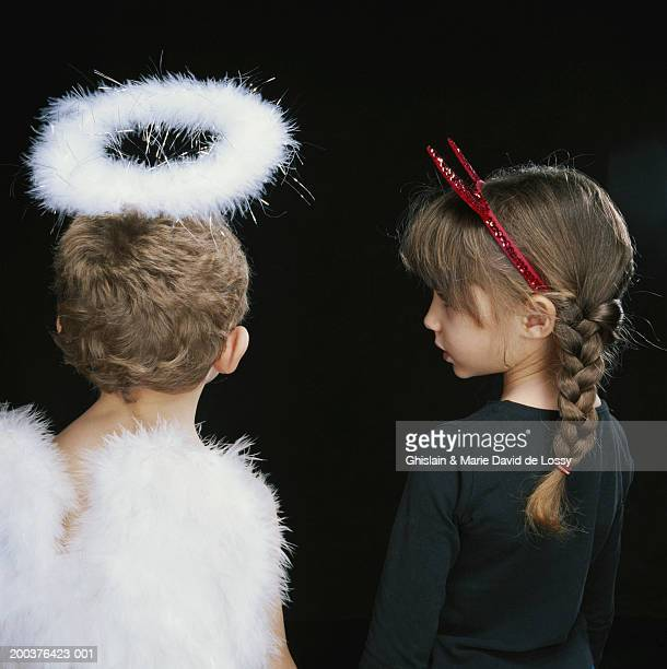 Boy and girl (2-6) wearing angel and devil costumes, rear view