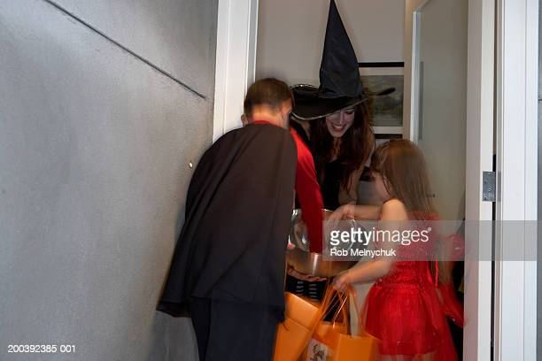 Boy and girl (8-10) wearing Halloween costumes, getting candy