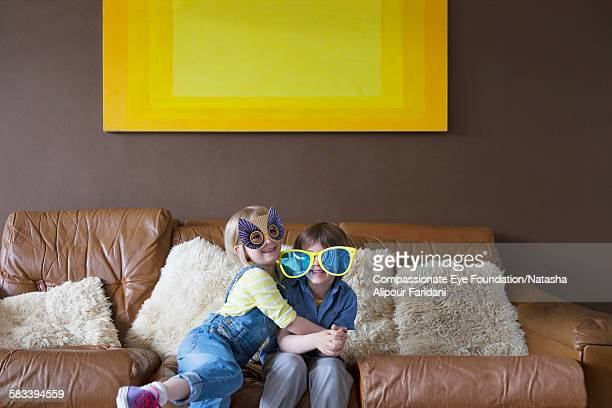 Boy and girl wearing oversized sunglasses and mask